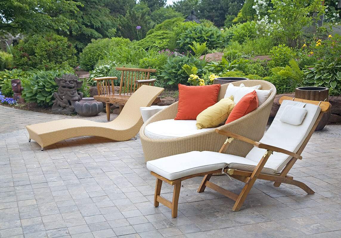 An array of modern wicker garden furniture on a patio in the home garden.